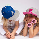 kids wearing letter caps and holding sunglasses