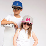 Letter caps on two kids a boy and girl aviator sunglasses