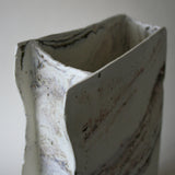 Porcelain clay vase handmade using clay found in the Roseland Peninsular, Cornwall, UK to give colour and interest showing the irregularity of the top edge
