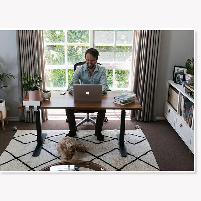 Man Sitting at Recycled Messmate Sit-Stand Desk