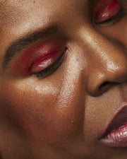 WOman with glossy red eyeshadow, red blush on cheeks