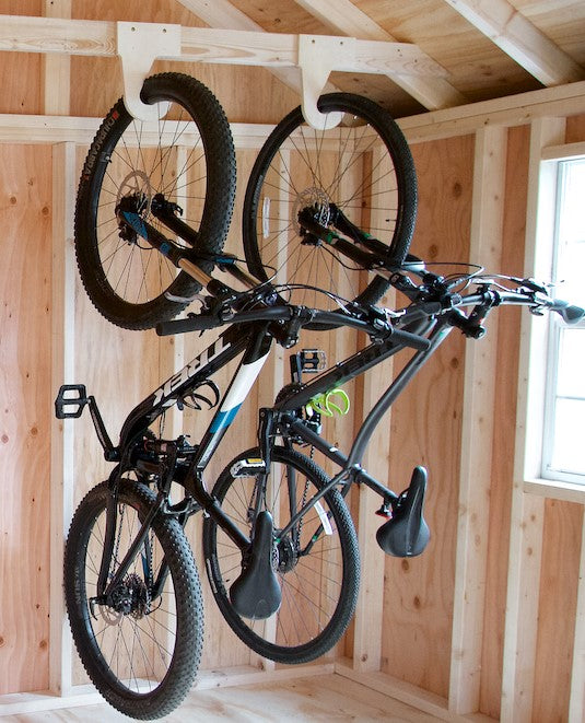 Two bikes hanging using the My S.O.S. bike organizers hanging by front wheel