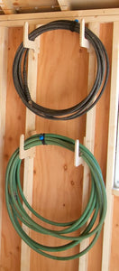 2 hoses hanging from hose organizers