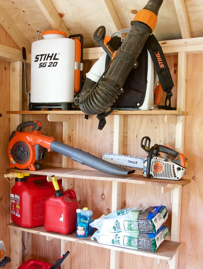 Shelving brackets with multiple tools and outdoor equipment on them