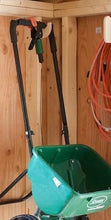 Load image into Gallery viewer, Lawn spreader hanging from a miscellaneous shed organizer