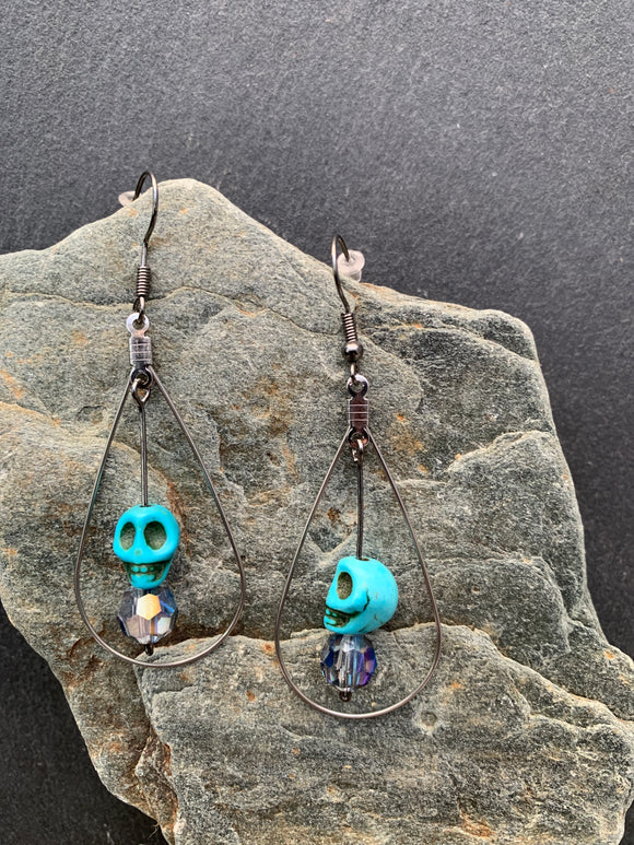 Turquoise skulls with glass crystal beads and tear drop surround.