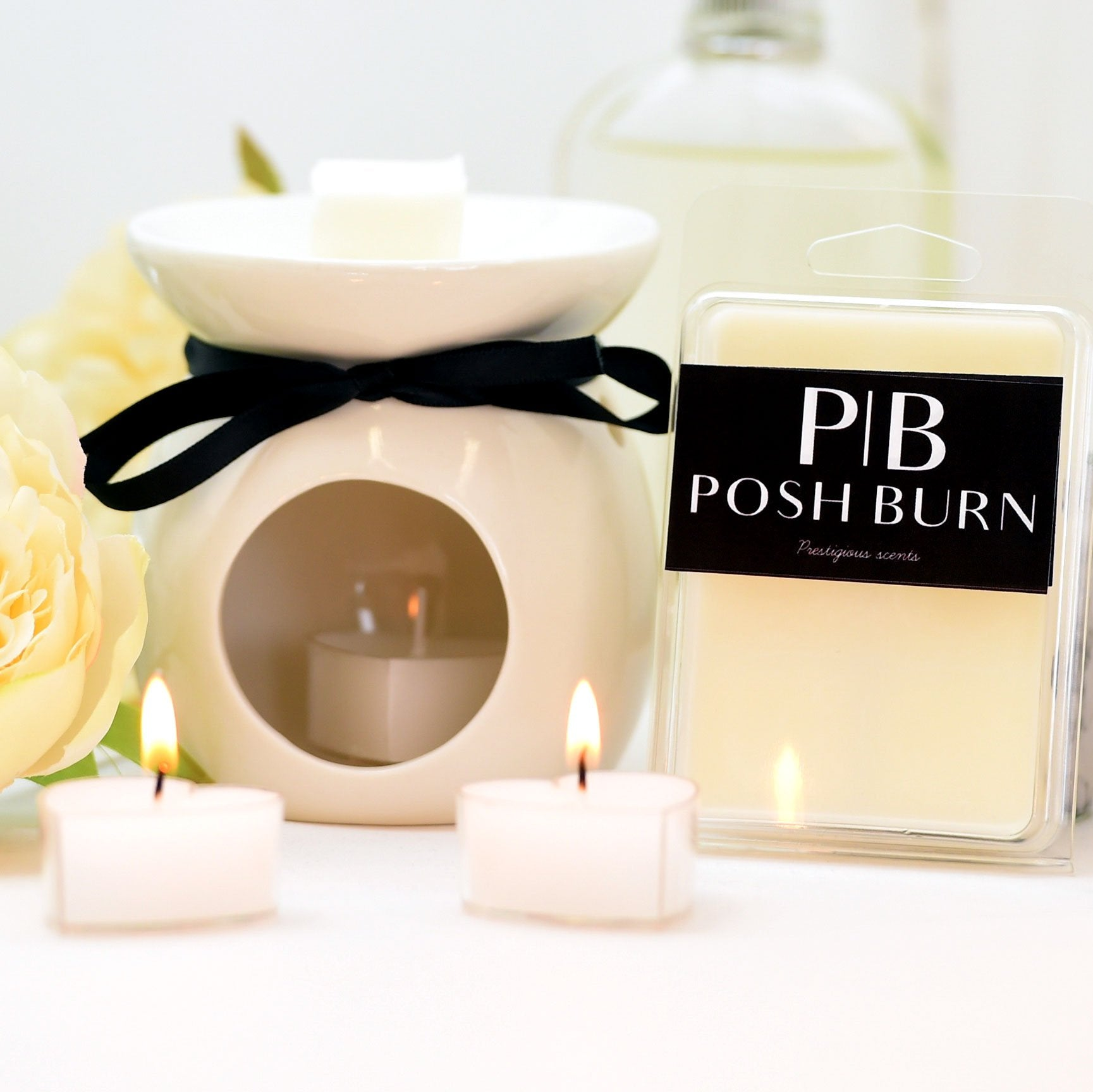 Ceramic waxmelt burner, shown with a packet of wax melts and Two candles