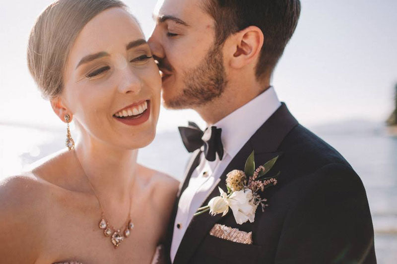 bride-groom-kissing-cheek-rose-gold-jewelry-wedding-fashion-tuxedo-bowtie-classic-bride