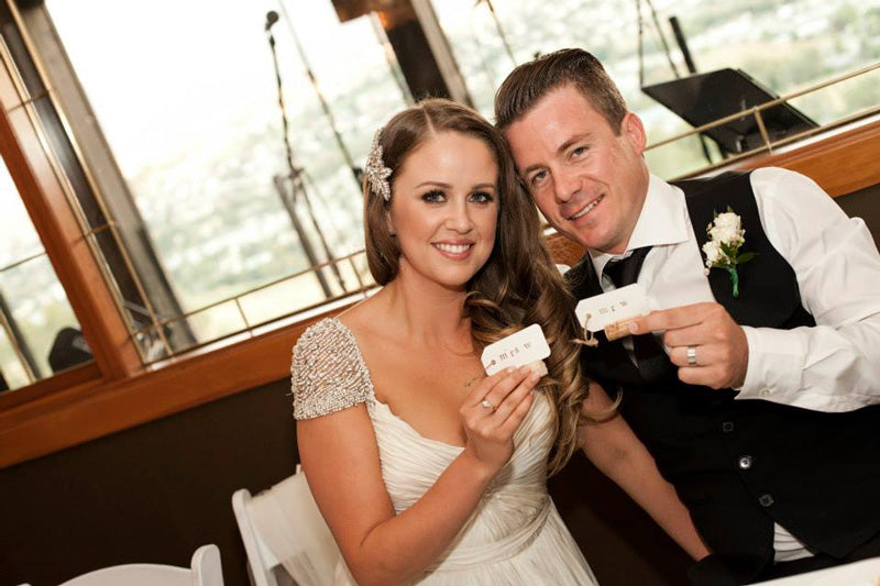 real bride and groom holding mr and mrs corkscrew placecard holders.