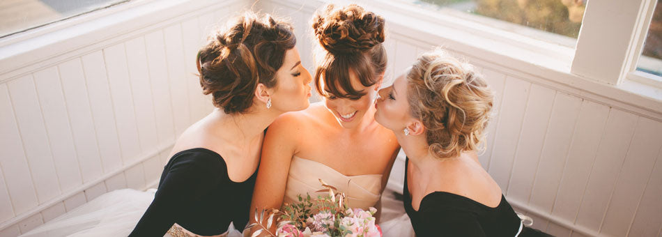 bride and bridesmaids kissing on cheek photography by ainsley rose