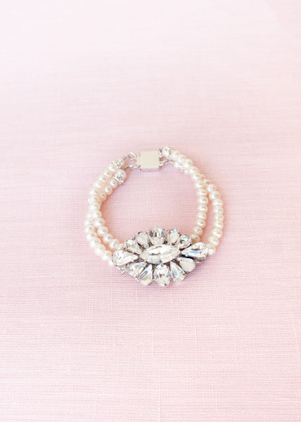 flat-lay of pearl and crystal brooch bracelet with two strands pearls