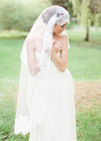 bride wearing chantilly lace mantilla veil with wide lace scallop detail