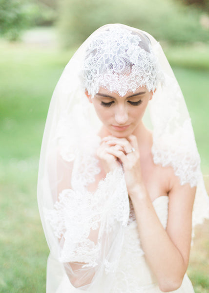 close up of bride wearing chantilly lace mantilla with wide border.