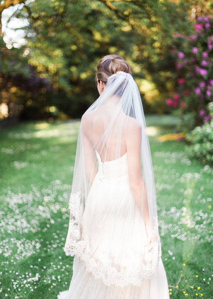 back view of bride wearing a fingertip chantilly lace veil.