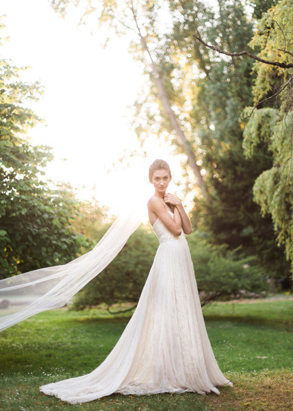 bride in lace veil and single layer tulle veil floating with sun through trees