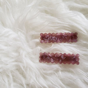 a pair of pink hair clips with scalloped edges