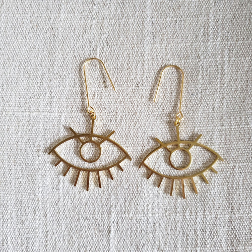 Large Eye Brass Earrings on woven fabric