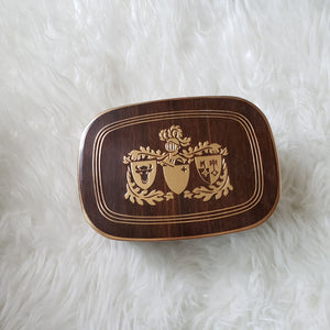 tin container featuring a knight and coat of arms