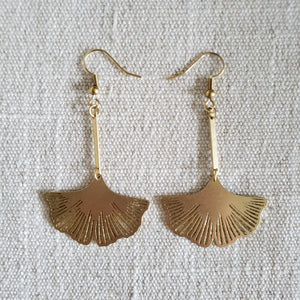 Ginkgo leaf brass earrings on woven fabric