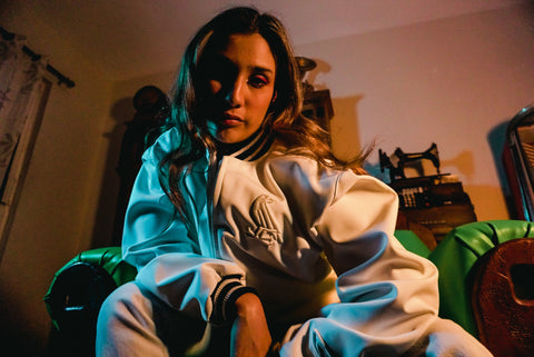 Female model wearing WHITE JACKET sitting on couch in neo phosphorescent lighting. Fifth image of collection.