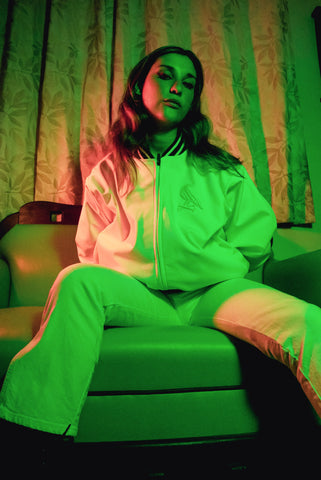 Female model wearing WHITE JACKET sitting on couch in neo phosphorescent lighting. Fourth image of collection.