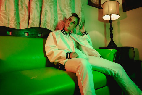 Female model wearing WHITE JACKET sitting on couch in neo phosphorescent lighting. Second image of collection.