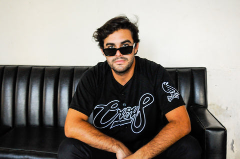 Model wearing the Classic B&W jersey & sunglasses, sitting casually on a black couch. Fifth image of collection.