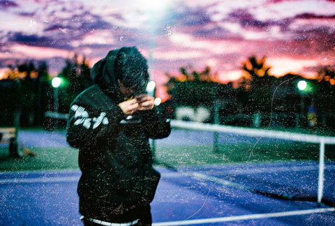 Man wearing Rainforrest hoodie by Crowdead, standing outside as the sun sets. Third picture.