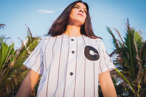 Girl wearing Referee II jersey outdoor in tropical setting.
