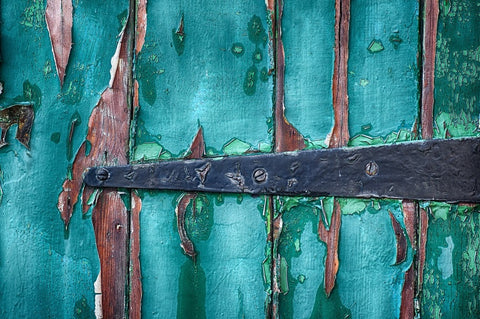 Old damaged green wooden door with a black iron hinge
