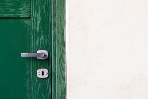 Image of a green door against a white stone wall.