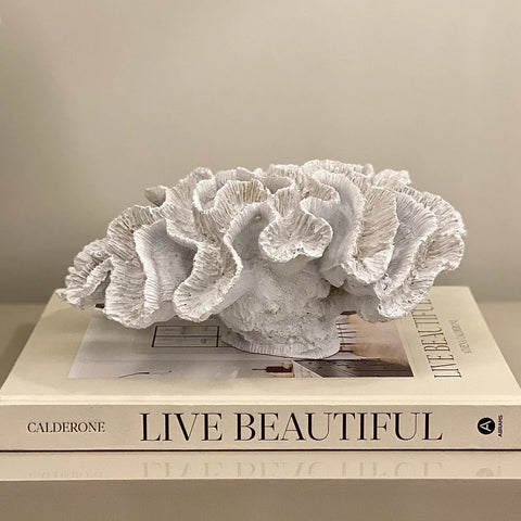 Styling a faux coral on a decorative book to draw attention on a coffee table