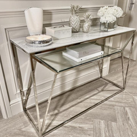 Layered designer books styled on a silver and marble console table