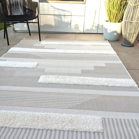 Leon Cream and Grey outdoor rug with abstract designs on a summery patio