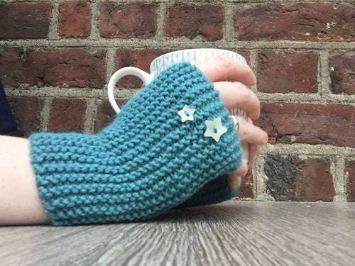 Bread and Buttoned Mitts in Rico Soft Merino Aran pictured with a Debbie Bliss Mug. Simple Fingerless Gloves pattern for beginner knitters.