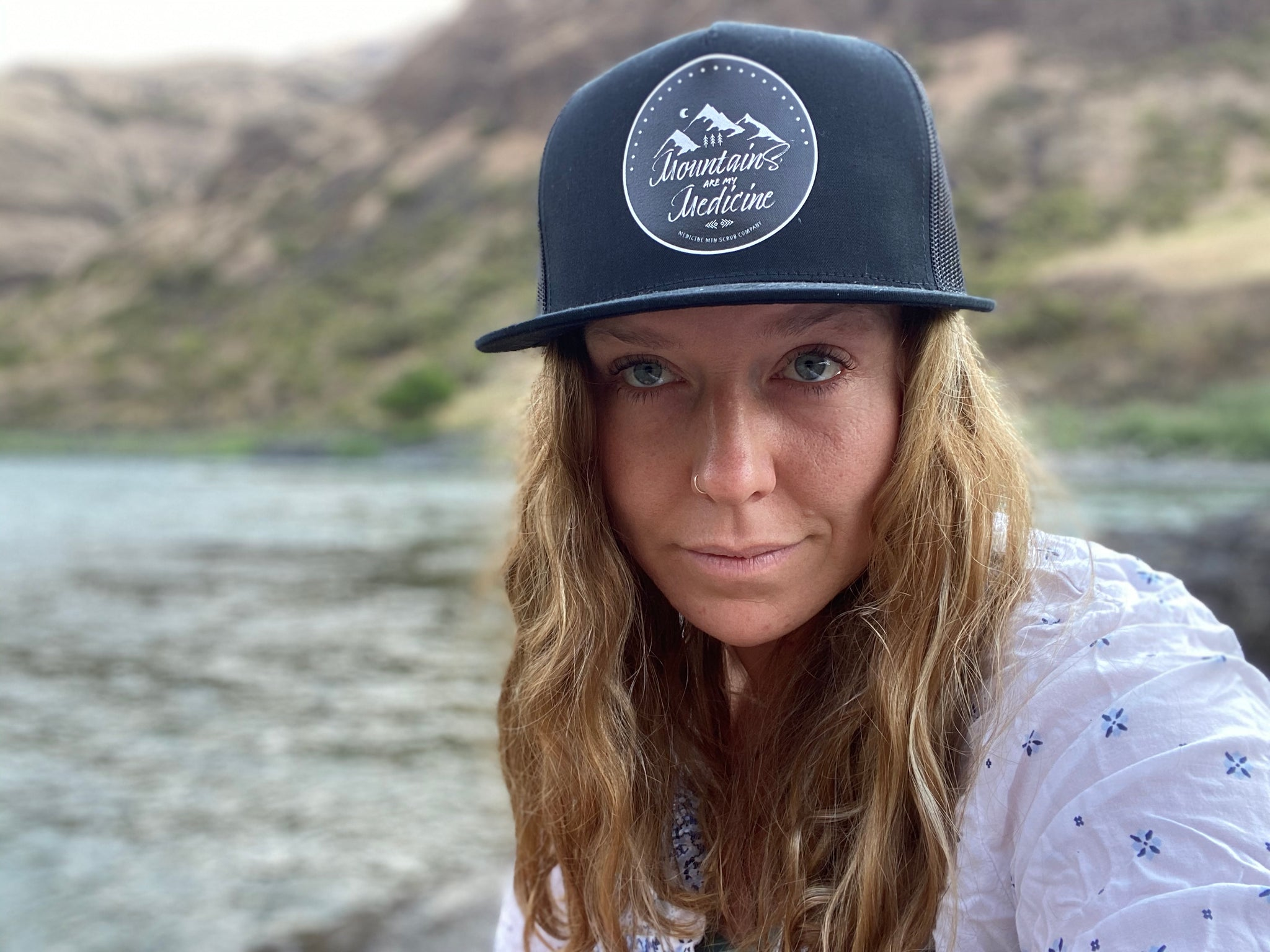 Mountains are my Medicine Logo trucker hat worn by Oriana Turley