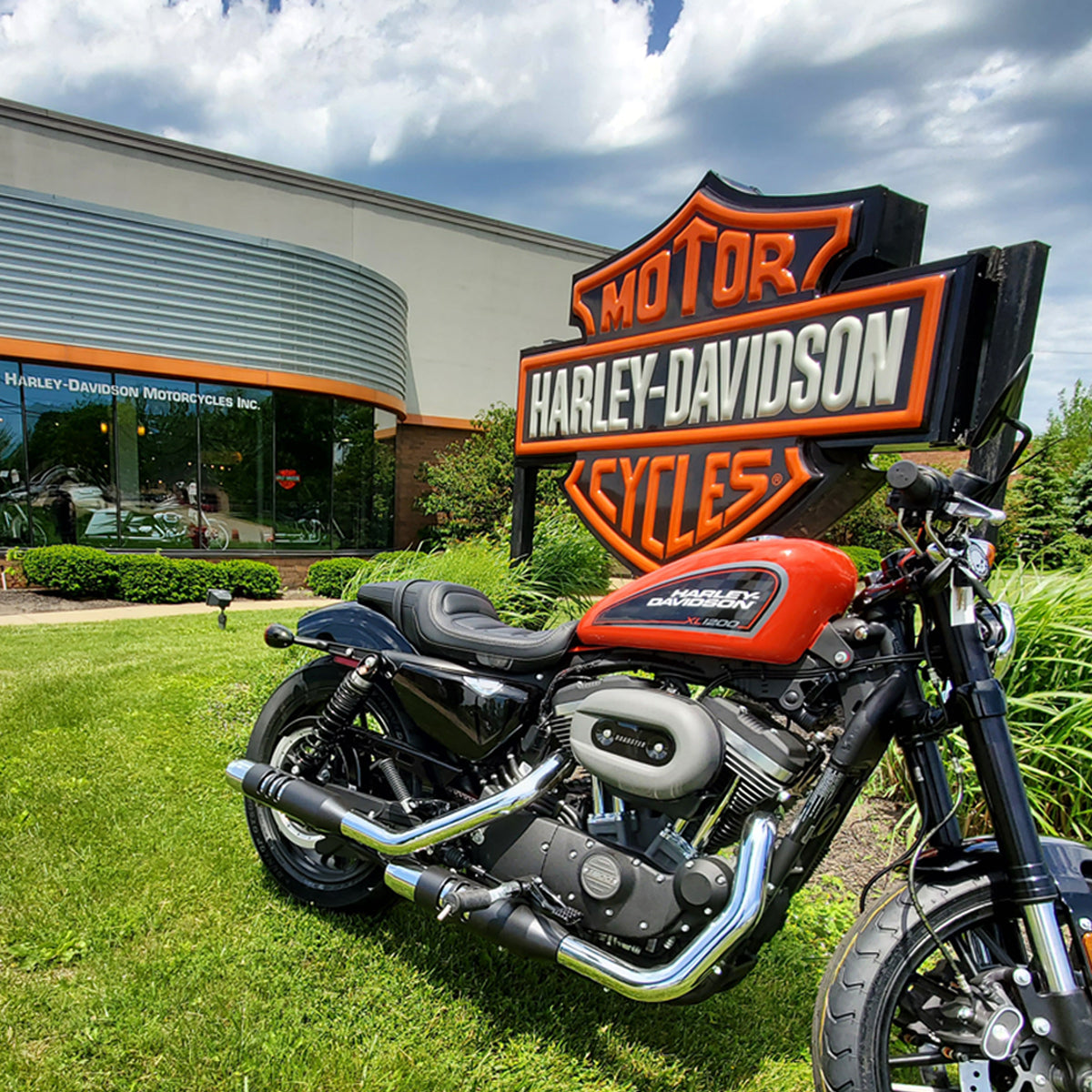 In front of Western Reserve Harley-Davidson with a performance orange Roadster posing by the bar & shield sign.