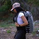 Female model wearing the Red Stripe™ Lycos Shield Backpack - Waxed Cotton