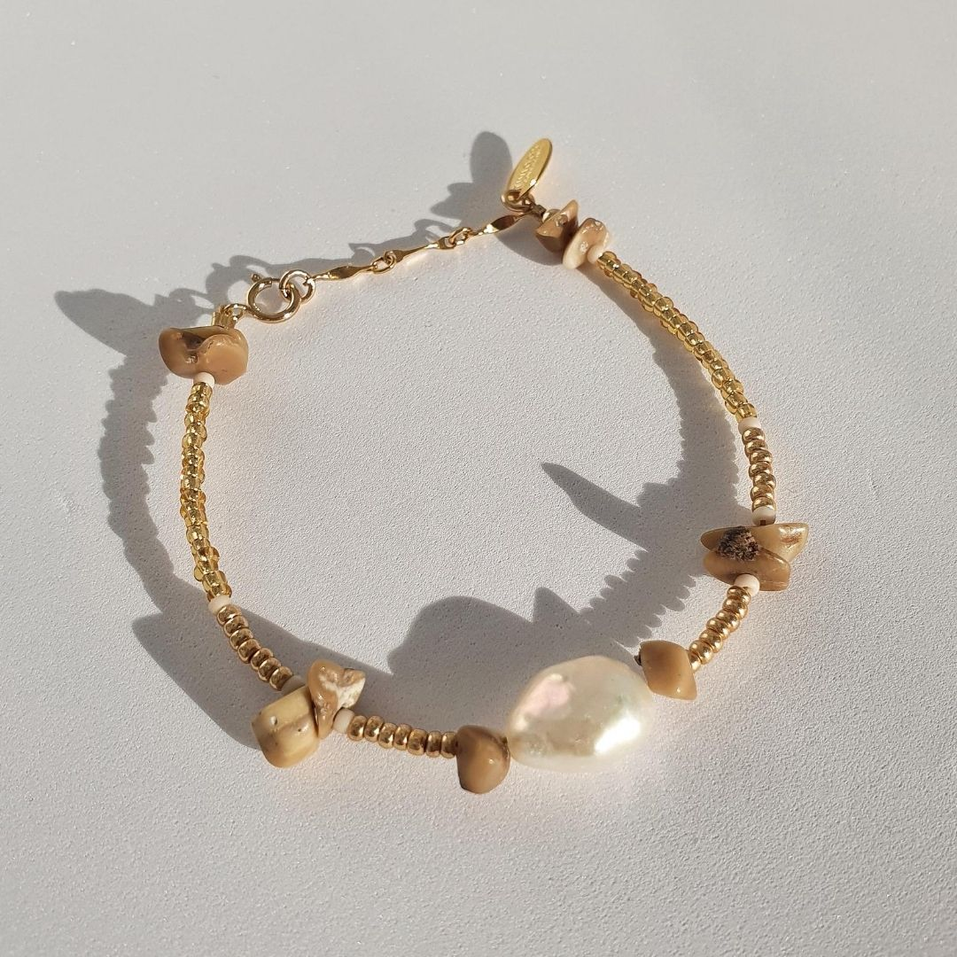 Designed with freshwater pearl, bamboo coral, glass seed beads and 14Kt gold-filled beads. Solo features a stunning large pearl, complimented by bamboo coral. A stand-out piece perfect on its own or part of a stack.