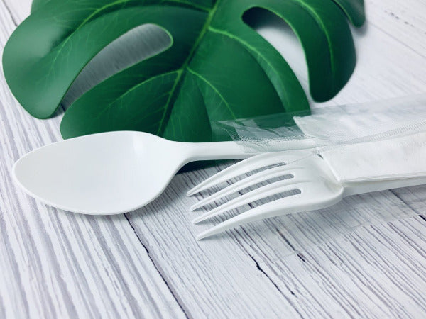 Spoon and fork on a wooden white table with a leaf
