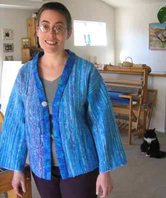 Lisa Rayner shows off her hand-made rag jacket as her cat Pablo looks on in the background.