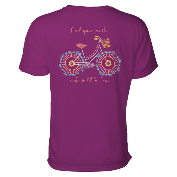 "Southern t shirt slogan is ""Find your path."" Design is whimsical illustrated bicycle in light blue, pink and cantaloupe on a boysenberry t-shirt"