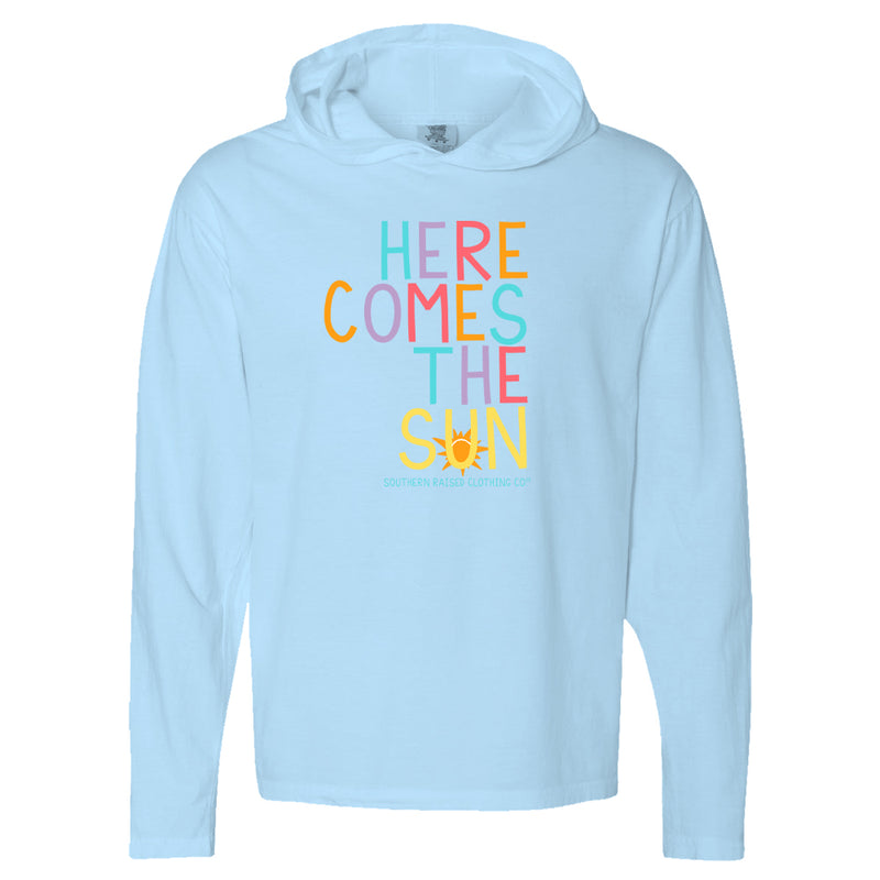"Long-sleeve blue hoodie with slogan ""Here Comes the Sun.""  Each letter rotates in color, blue, purple, pink, cantaloupe. The word Sun is in all yellow with graphic of orange sun."