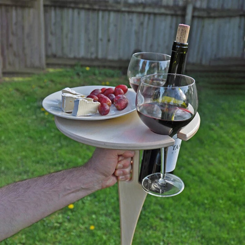 Folding picnic table holding two wine glasses and food pairing