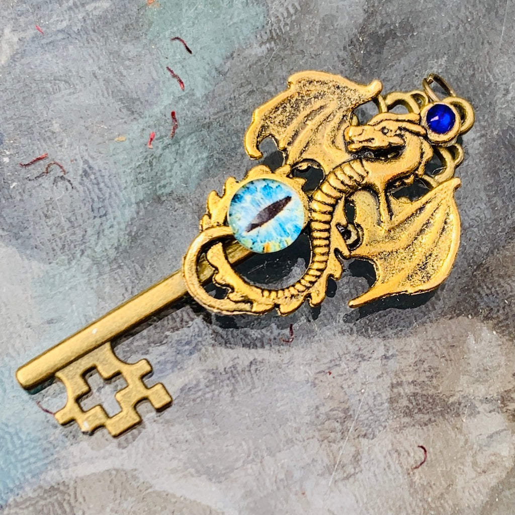 An image of the Antique Gold Dragon Skeleton Key Necklace from Uncorked & Bottled Up on a glass background