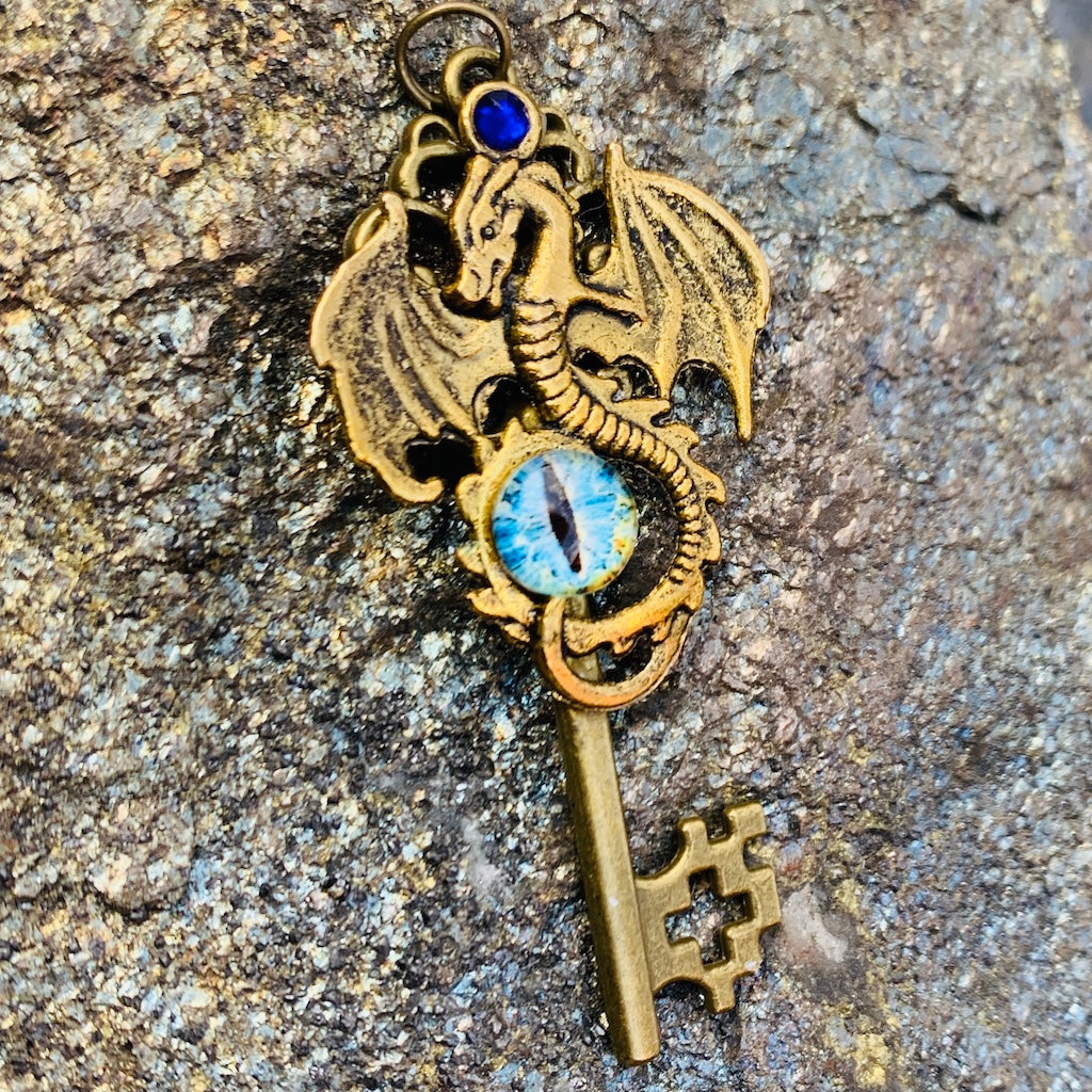 An angled image of the Antique Gold Dragon Skeleton Key Necklace from Uncorked & Bottled Up on a stone background