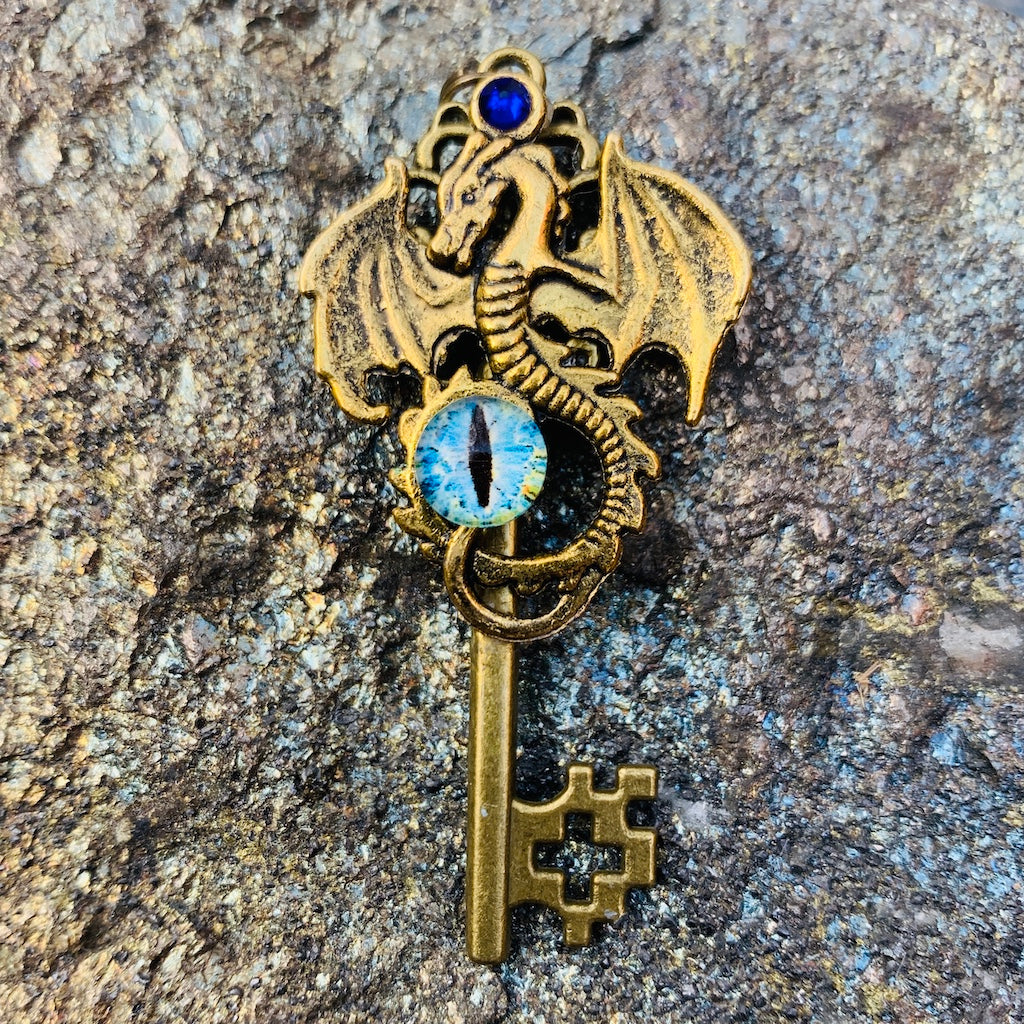 An image of the Antique Gold Dragon Skeleton Key Necklace from Uncorked & Bottled Up on a stone background