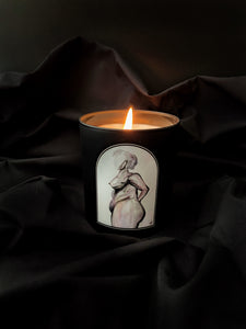 soy candle in a black glass jar with an arch nude female figure study water color painting nudesse candle that is lit up with a black background