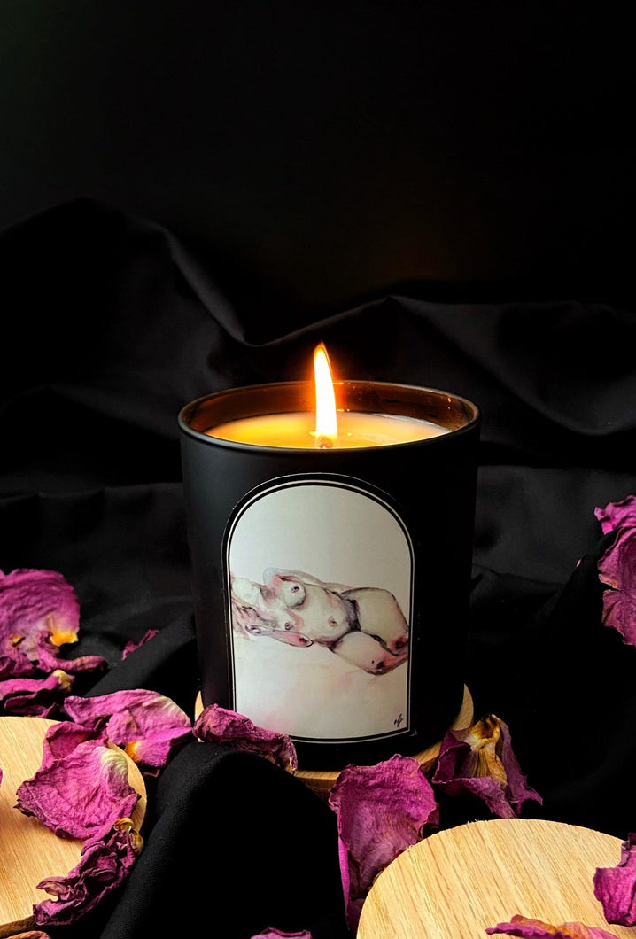 Soy candle in a black jar with a nude figure study water color painting label lit up candle with black background with dry roses