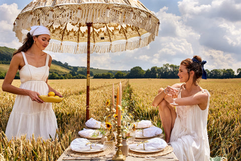 Friends enjoying a beautiful tablescape within wheat fields and under a parasol